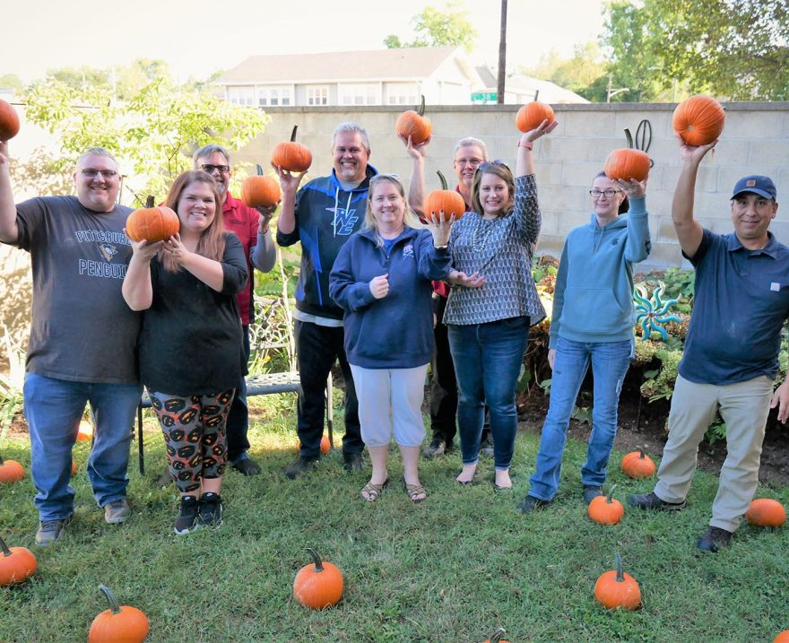 Group of people holding up pumpkins