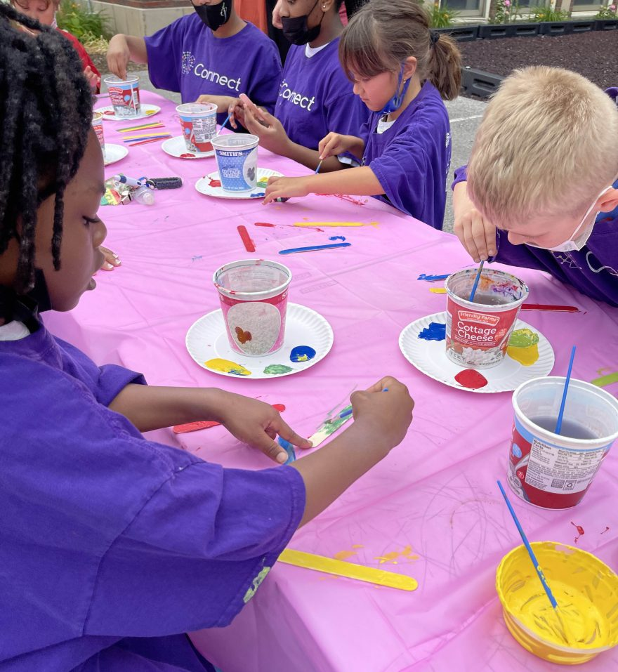 Children painting popsicle sticks